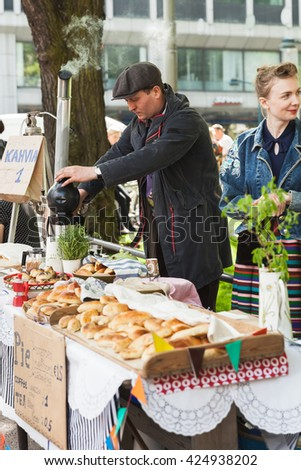 Helsinki, Finland - May 21, 2016: Helsinki Restaurant Day 2016. It is traditional street carnival of food. Participants sign up on the website and get cooking. Young positive man with samovar and pies