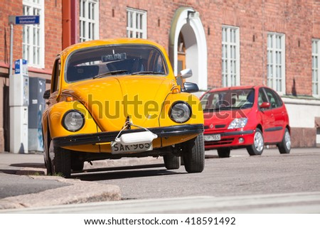 Helsinki, Finland - May 7, 2016: Old yellow Volkswagen beetle is parked on a roadside, front view - stock photo