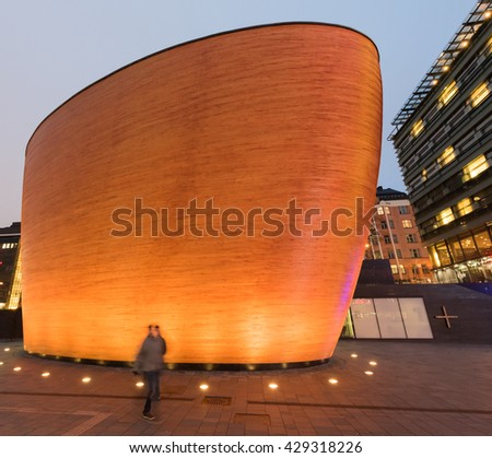 HELSINKI, FINLAND - 20 NOVEMBER 2015: A woman walks in front of the Kamppi Chapel of Silence in the nordic late afternoon light.
