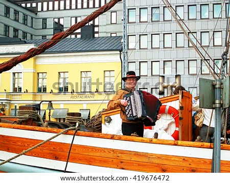 HELSINKI, FINLAND - OCTOBER 7, 2006: Unidentified man plays the accordion on an embankment in Helsinki, Finland. The old embankment is a pier with yachts in old town, the famous place among tourists