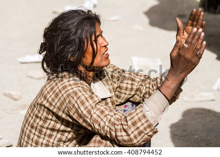 Hemis, India - June 29:  homeless beggar women with outstretched arms asking for alms from visitors of the Cham Dance Festival of Tibetan buddhism on June 29, 2012 in Hemis monastery, India. - stock photo