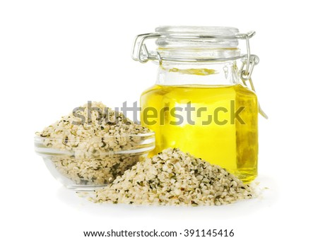 Hemp oil in a bottle and hemp seeds closeup isolated on white background - stock photo
