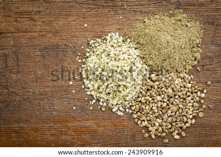 hemp seed, hearts and protein powder - small piles on a grunge wood - top view - stock photo