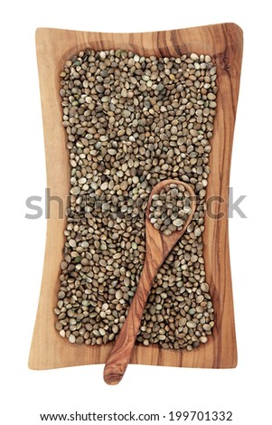 Hemp seed in an olive wood bowl with spoon isolated over white background. - stock photo