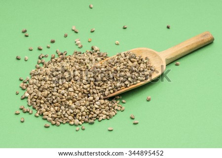 Hemp seeds and a wooden spoon on a light green color seen from above - stock photo