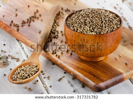 Hemp seeds on a wooden board. Selective focus - stock photo
