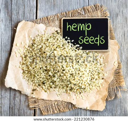 Hemp seeds on wooden table with small chalkboard - stock photo