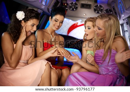 Hen party in limousine, girls looking at her friends engagement ring.?