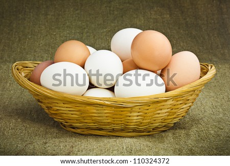 Hen's Eggs in a Woven Straw Basket on a Sacking background - stock photo