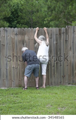 Her husband helps her peek over the fence to see what the neighbors are up to! - stock photo