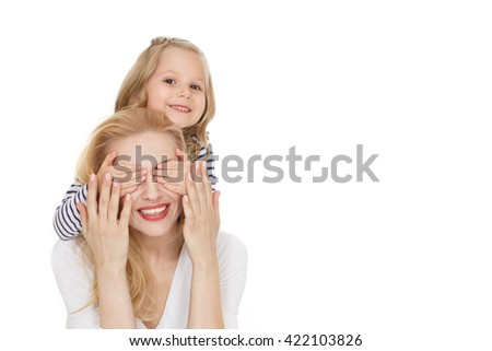 Her lovely mommy. Shot of cheerful little girl covering her mothers eyes with her hands looking to the camera smiling isolated on white. - stock photo