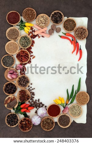 Herb and spice abstract border over parchment and lokta paper background. - stock photo