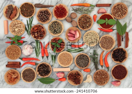 Herb and spice collection in wooden bowls and loose over marble background. - stock photo