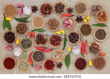 Herb and spice collection in wooden bowls and loose over old grunge paper background. - stock photo