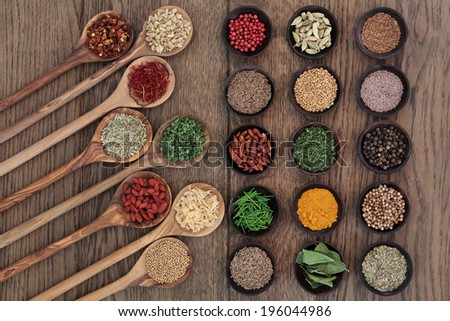 Herb and spice food seasoning selection in wooden spoons and bowls over oak wood background. - stock photo