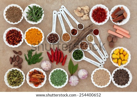 Herb and spice selection in measuring spoons and crinkle bowls. - stock photo
