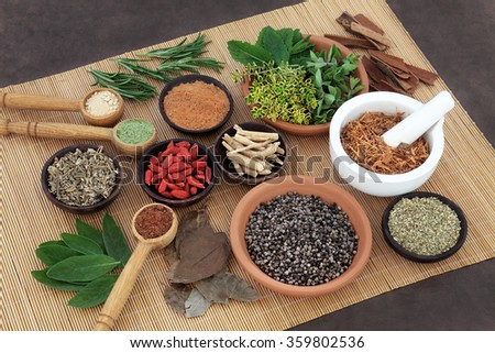 Herb and spice selection used in herbal health for men on bamboo mat. - stock photo