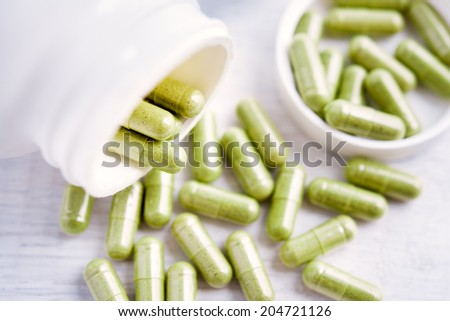 Herb capsule spilling out of plastic bottle - stock photo