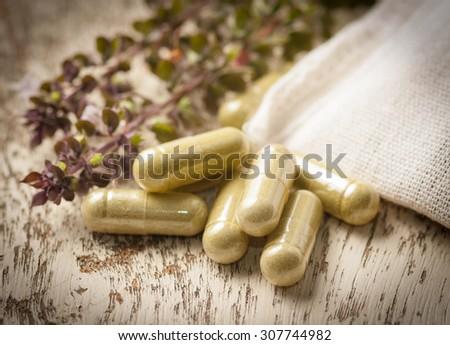 Herb capsule with green herbal leaf on wood - stock photo