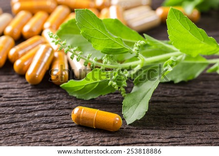 herb capsule with green herbal leaf on wood table. - stock photo