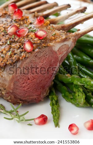 Herb crusted rack of lamb garnished with asparagus, green grapes, and pomegranates. Mini pumpkins and fresh fruits.  - stock photo