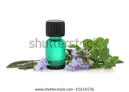 Herb leaf sprigs of sage, oregano and rosemary leaf and flower sprigs with green aromatherapy essential oil glass bottle, isolated over white background with reflection. - stock photo