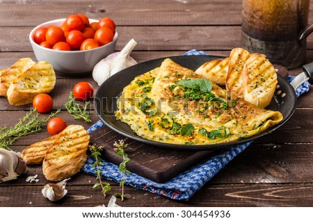 Herb omelette with chives and oregano sprinkled with chili flakes, garlic panini toasts - stock photo