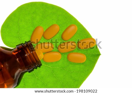 Herb pill with green herbal leaf and bottle isolated with clipping path - stock photo