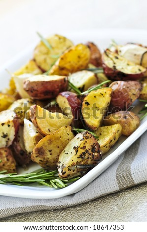 Herb roasted potatoes served on a plate - stock photo