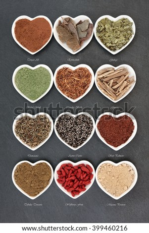 Herb selection for mens health used in natural alternative herbal medicine in heart shaped white porcelain dishes over slate background with titles. - stock photo