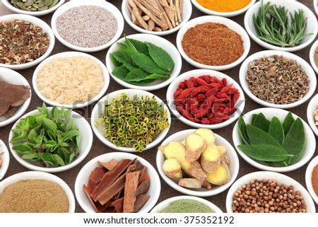 Herb, spice and super food selection for mens health in porcelain bowls over hessian background. Used in natural alternative herbal medicine. Selective focus. - stock photo
