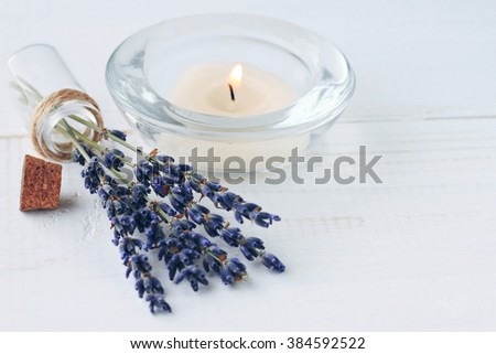 Herbal aromatherapy.  Aroma candle, dried lavender flowers on wooden table. Home refreshing, beauty fragrance. Blue toned. - stock photo