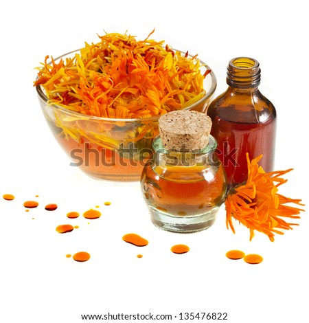 herbal calendula in the glass and aromatherapy essential oil Isolated white background - stock photo