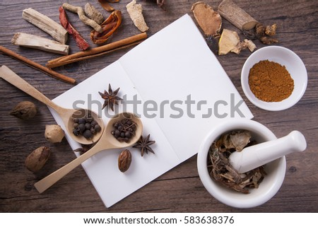 Herbal medical with white mortar and notebook, education concept.