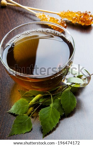Herbal medicine: Cup with tea and birch branch - stock photo