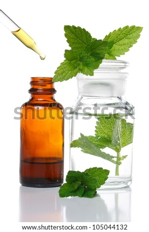Herbal medicine dropper bottle with mint leaves - stock photo