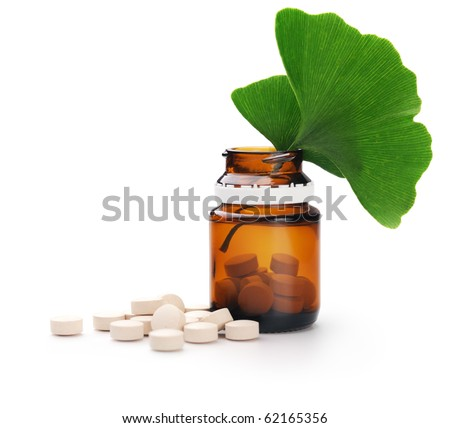 Herbal medicine. Ginkgo leaves and tablets n a bottle. Isolated over white background - stock photo