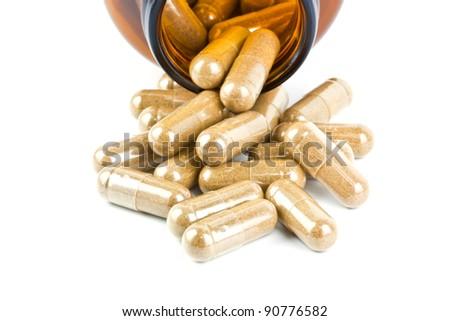 Herbal medicine pills spilling from bottle - stock photo