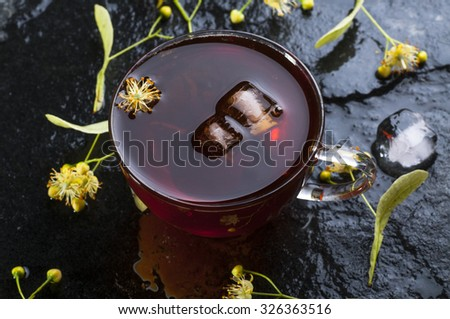 Herbal medicine series: Linden tea with ice cubes in cup  and flowers on black stone background - stock photo