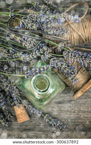 Herbal oil essence and dried lavender flowers. Vintage still life. Top view. Retro toned picture. Selective focus with bokeh effect - stock photo