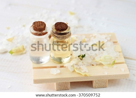 Herbal spa cosmetic products. Essential oils, soap bar, sea salt. Soft focus, light creamy tones. - stock photo