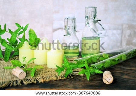 Herbal spa with essential oils of mint and candles - stock photo