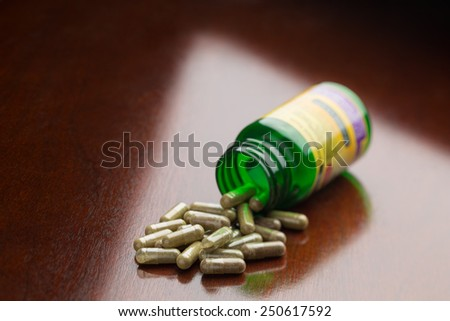 Herbal supplement capsules spilled from a bottle onto a table. Shallow depth to field. - stock photo