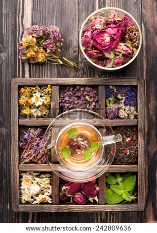 Herbal tea and dried herbs in a wooden box - stock photo