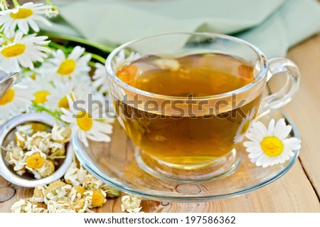 Herbal tea in a glass cup, metal sieve with dry chamomile flowers, fresh flowers, daisies, green cloth on a background of wooden boards - stock photo