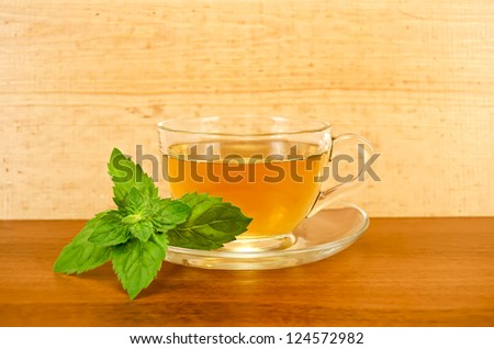 Herbal tea in a glass cup with a sprig of mint on the background of wooden boards - stock photo