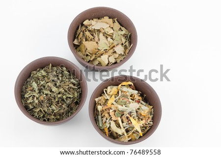 Herbal tea in small clay teacups on white background. - stock photo