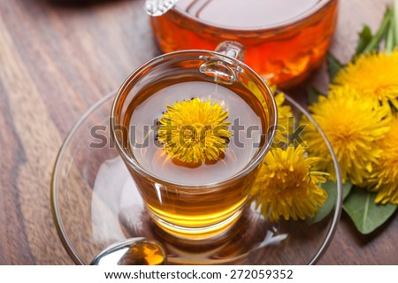 herbal tea made of fresh dandelion essence, with honey, blossoms and green leaf on wooden table - stock photo