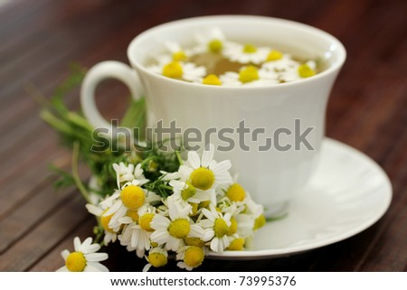 herbal tea with chamomile on a wooden table ,shallow dof - stock photo