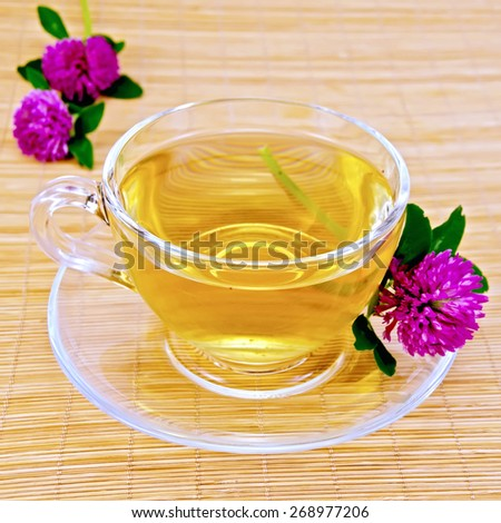 Herbal tea with flowers of clover in a glass cup on a bamboo napkin - stock photo